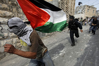 An Israeli policeman chases a stone thrower in East Jerusalem, October 9, 2009. (Darren Whiteside/Reuters/Landov)